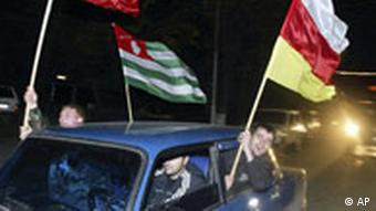 People wave flags from a car of, from left, of Russia and the two Georgian breakaway provinces, Abkhazia and South Ossetia