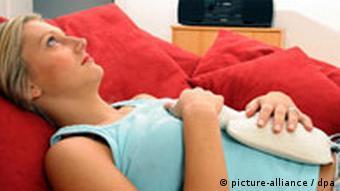 Frau liegt auf dem Bett, hat eine Wärmflasche auf dem Bauch. Quelle: dpa