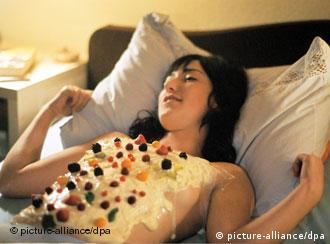 Szene aus Eden: Die Kellnerin Eden (Charlotte Roche) liegt mit Creme und Beeren garniertem Oberkörper im Bett