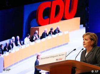 Merkel speaking at a party conference, with other delegats and a CDU logo seen on a screen next to her