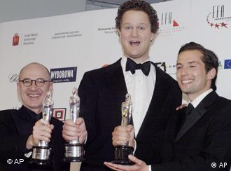 Germany's Ulrich Muehe , left, poses with his award for best actor with Florian Henckel von Donnersmarck ,center, with his award for best screenwriter and producer Qvirin Berg , right, after the European Film Awards in Warsaw ,Poland