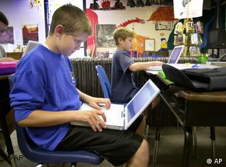 A boy sits with a notebook computer on his lap