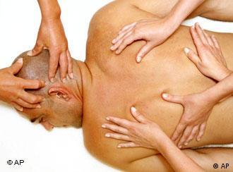 Ein nackter Mann wird von vielen Händen am Kopf und am Rücken massiert