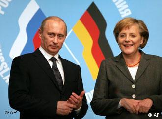 German Chancellor Angela Merkel, right, and Russian President Vladimir Putin stand together during a signing ceremony of economic contracts at the German-Russian summit in Tomsk in 2006