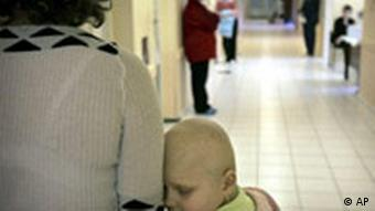 A Ukrainian girl suffering from cancer waits to receive treatment with her mother at the children's hospital in Kiev