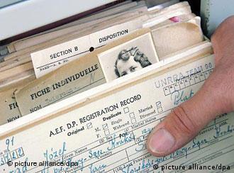 Hand hält Stapel von Nachkriegszeit-Dokumenten ehemaliger Zwangsarbeiter und Verfolgter des NS-Regimes (Quelle: dpa)