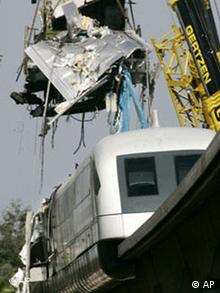 Parts of badly damaged Transrapid train being removed by crane