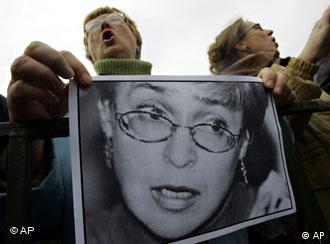 Demonstrators hold a photo of Anna Politkovskaya during a rally on Pushkin square in downtown Moscow