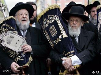 Jewish rabbis carry Torah scrolls in a solemn procession from the old synagogue to the new one in downtown Munich
