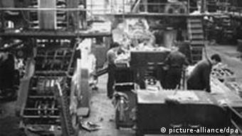 Männer arbeiten in einer Halle an Rotationsmaschinen