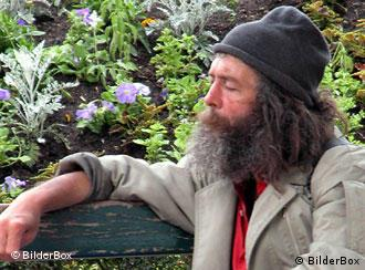 A bearded, homeless person sitting on a park bench