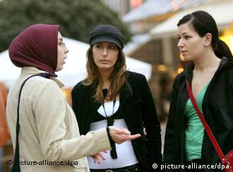 A young woman wearing a headscarf speaking to two women without a headscarf