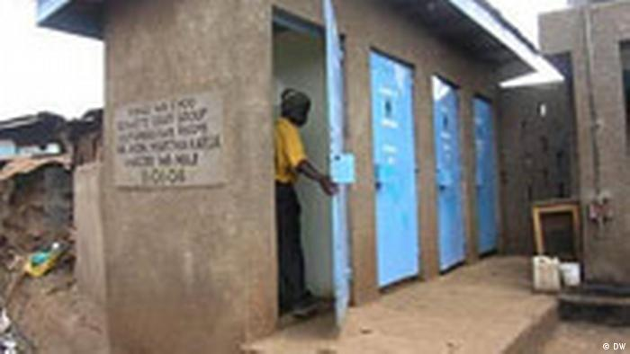 A ma   n goes into a cubicle in a toilet block in Kibera