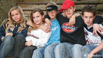 Eine Gruppe von Jugendlichen sitzt nebeneinander auf einer Treppe