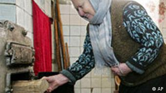 A Belarusian woman puts wood into a stove