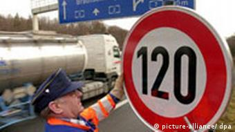 A worker mounts a 120 km/hour sign on a German highway