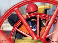 Рабочий закруивает большой газовый вентиль на компрессорной станции