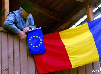 An elderly Romanian pins the EU flag to a Romanian flag hanging from his balcony