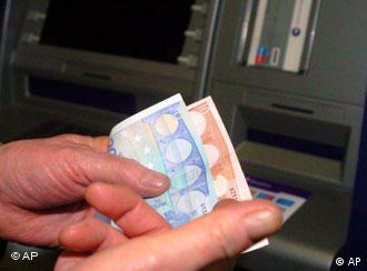 A hand holding euro notes in front of an ATM machine