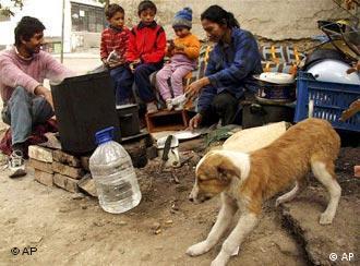Eine Roma Familie mit drei Kindern sitzt im Freien (Quelle: AP)
