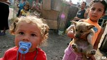 Young gipsies play with a dog in front of their home in a ghetto in Bulgarian capital Sofia, Friday, June 30, 2006. The ghetto was to be destroyed Friday but under pressure by human rights activists, authorities canceled plans to destroy dozens of allegedly illegally built houses in this Roma ghetto in downtown Sofia. (AP Photo/Petar Petrov)