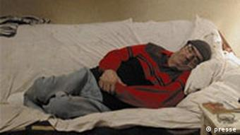 A scene from The Death of Mr. Lazarescu sees a man lying sideways on a couch looking miserable
