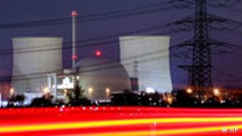 Das kugelförmige Atomkraftwerk Biblis im Abendlicht, flankiert von den Kühltürmen links und rechts. Im Vordergrund ein t-förmiger Strommast mit zahlreichen Kabeln (Foto: AP)