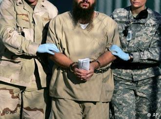 A shackled detainee is transported on the grounds of Camp Delta detention center, Guantanamo Bay
