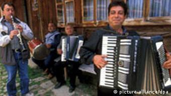 Eine Gruppe von Sinti und Roma musiziert vor einem Haus (Quelle: dpa)