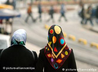 Two women with headscarves walk down a street