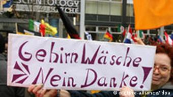 A sign reading Brainwashing -- No thanks is held up in front of Scientology's Berlin office