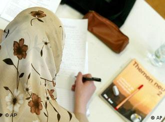 A woman in a headscarf writes during a language course