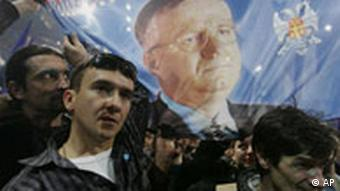 Supporters of the ultra-nationalist SRS-Serbian Radical Party display a flag showing party leader Vojislav Seselj, who is awaiting a trial at the U.N. war crimes court in The Hague, Netherlands, during a pre-election rally, Tuesday, Jan. 16, 2007, in Belgrade, Serbia. Parliamentary elections in Serbia are scheduled for January 21. (AP Photo/Srdjan Ilic)