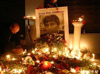 A Turkish man lights candles in front of a picture of slain journalist Hrant Dink