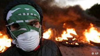A Hezbollah supporter, uses a Lebanese flag to cover his face as he walks in front of burning tires