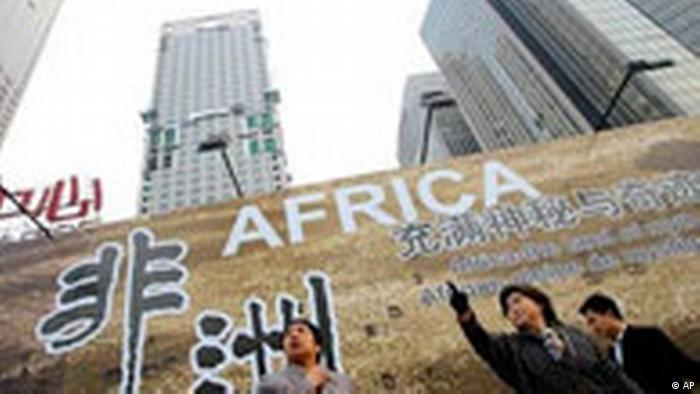Chinese woman stand in front of a billboard which promotes the upcoming China-Africa summit meeting, outside a hotel in Beijing Thursday Oct. 26, 2006. Beijing is making unusually lavish efforts to welcome leaders and officials from 48 African nations this week for a landmark summit meant to highlight China's huge and growing role in Africa. The Chinese characters at left read Africa. (AP Photo/Greg Baker)