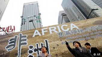 Chinese woman stand in front of a billboard which promotes the upcoming China-Africa summit meeting, outside a hotel in Beijing Thursday Oct. 26, 2006(Photo: AP Photo/Greg Baker)
