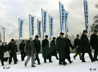 Shareholders walking past Siemens' flags on their way to an assembly