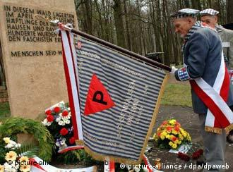A man with a concentration camp inmate flag stands in front of a memorial stone at Belower Wald