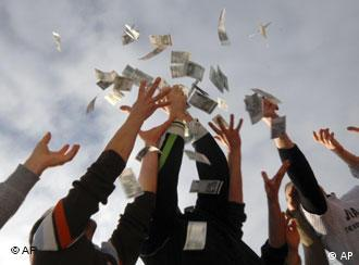 Arms of people reaching up to grab money being thrown
