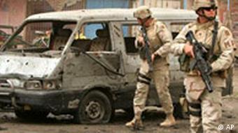 US soldiers inspect the scene of a massive suicide car bomb explosion targeting a US military convoy in Baghdad