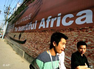 Pedestrians walking past an African poster