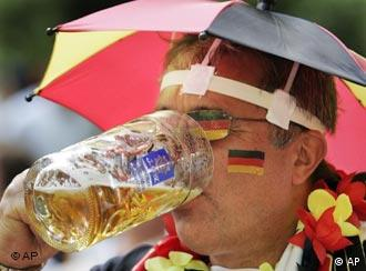 A man covered in Germany's national colors drinks beer