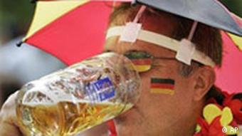 A man drinks beer in a Germany outfit with a head umbrella and face paint