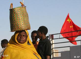 A Sudanese woman walks past a Chinese flag