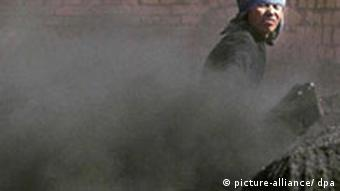 A person shovels black powder into a coal mill in a cloud of black dust