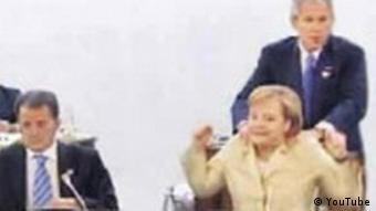 YouTube screenshot of Bush massaging Chancellor Merkel's shoulders while she's seated in a chair