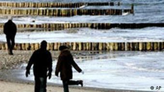 Strollers walkinh anlong a Baltic Sea beach in Germany