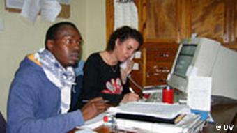 Afrikaner neben Europäerin bei Arbeit am Computer