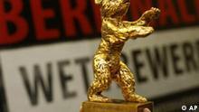 Ein Berlinale-Mitarbeiter zeigt einen Dummy des Goldenen Baeren vor einem Plakat der 57. Internationalen Filmfestspiele Berlinale in Berlin am Dienstagabend. 6. Februar 2007. 26 Filme werden im Wettbewerbsprogramm der Berlinale vom 8. bis 18: Februar 2007 gezeigt, 22 der Kinofilme konkurrieren um den Goldenen Baeren. (AP Photo/Markus Schreiber) --A Berlinale staff member holds a Golden Bear figure in front of a poster of the 57th International Film Festival 'Berlinale' in Berlin on Tuesday evening Feb. 6, 2007. The Berlinale takes place in the German Capital from Feb. 8 through Feb. 18, 2007. 22 films compete for the Golden and Silver Bears. (AP Photo/Markus Schreiber)